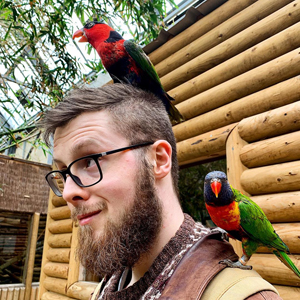 Photo of Tom Jameson with parrots on his head and shoulders