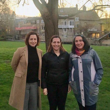 3 female postdocs standing near the millpond in Cambridge