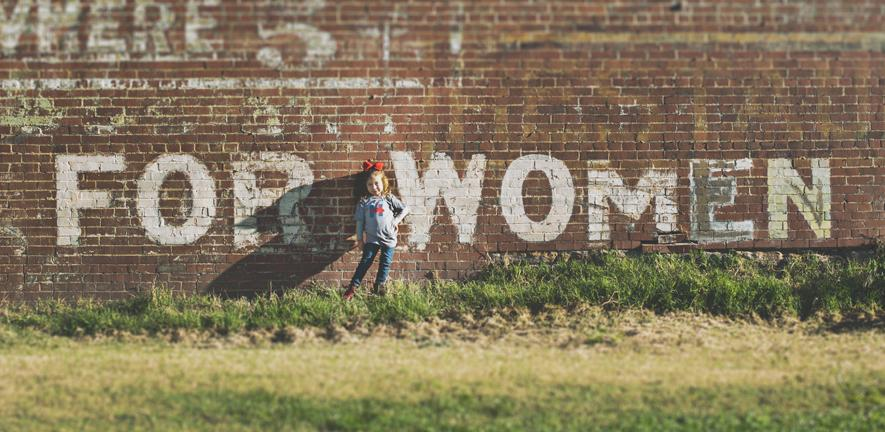 """girl standing in front of a red brick wall which has grafitti on saying """"for women"""""""
